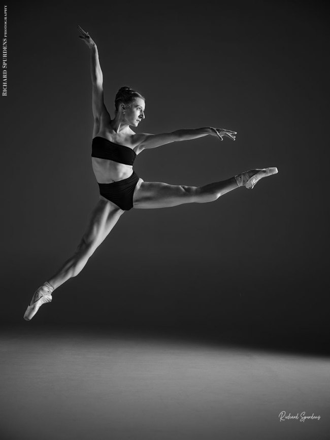 Dance Photographer - monochrome image of dancer leaping in a star jump towards the light