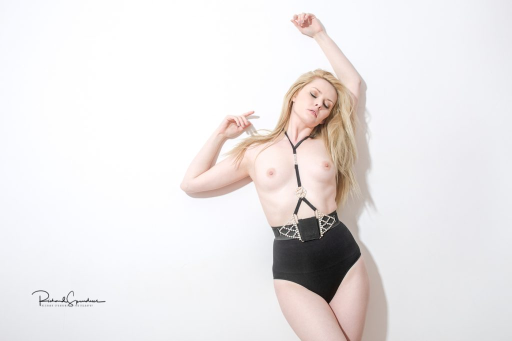richard spurdens photography image of model carla monaco topless wearing big black pants and jewelled belt leaning against a white wall