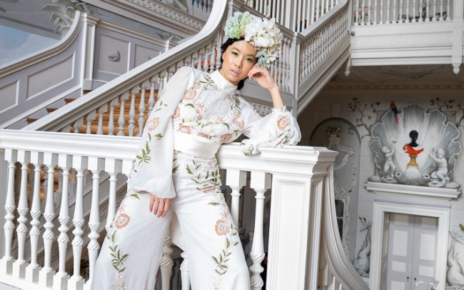 an interior shot of the model wearing a white trouser suit and floral head piece in the white stair way