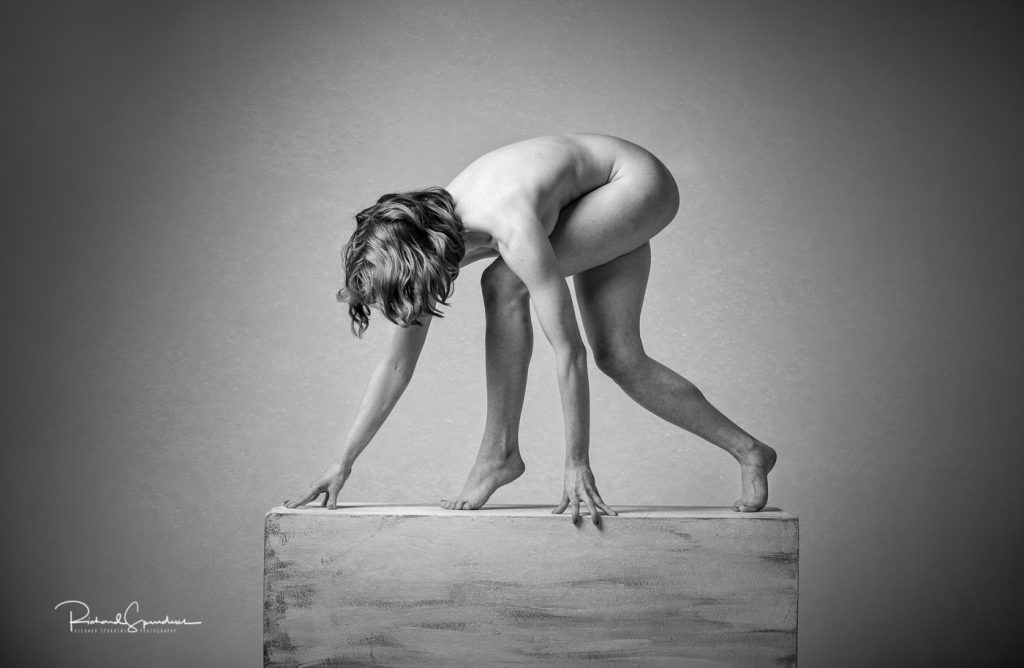 monochrome image showing a stong artistic nude figure shape standing on a plinth