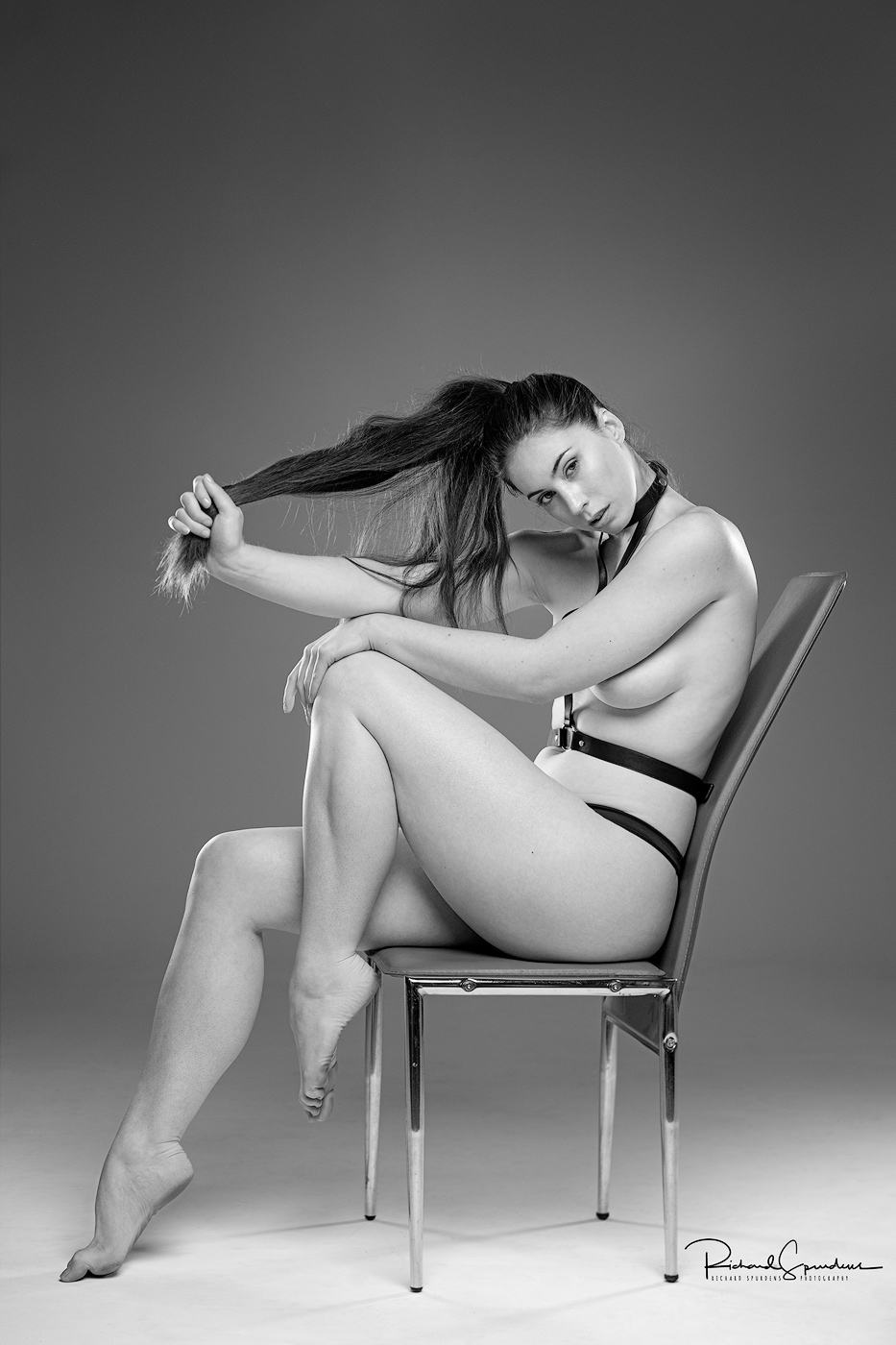 monochrome image of model elle beth wearing a simple black leather harness and posing on a modern metal chair holding her long hair in one hand and the other resting on her knee looking towards the camera