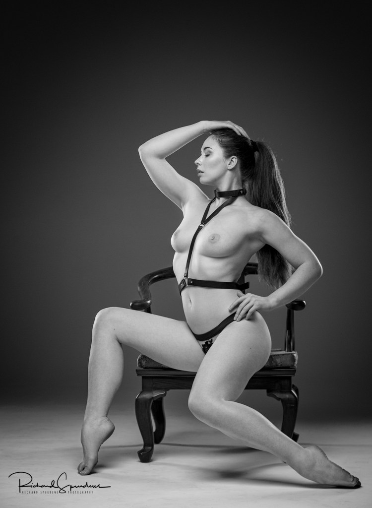 monochrome image of model elle beth wearing a simple black leather harness and posing across the edge of a chair with hands on her head and hips to create a strong figure shape