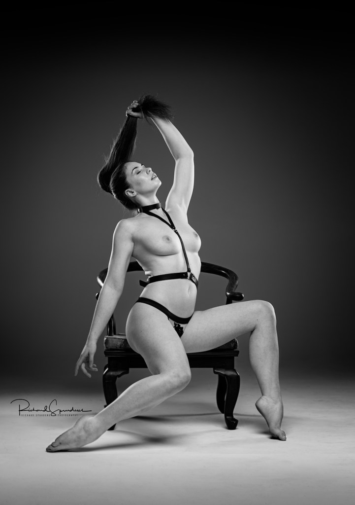 monochrome image of model elle beth wearing a simple black leather harness and posing on a low captains chair- holding her long hair up towards the ceiling and making a strong figure shape