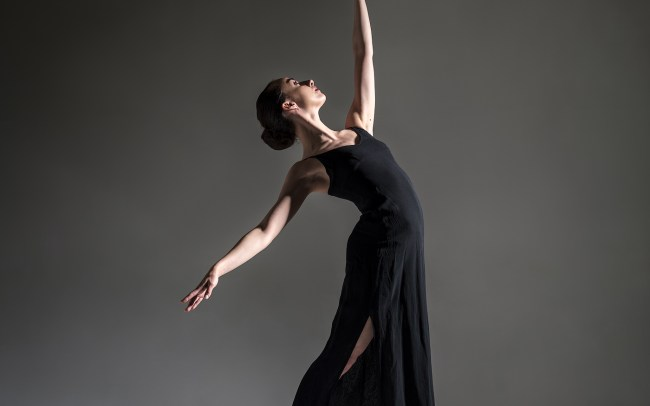 colour image of dancer Erica Mulkern facing into the light and reaching up to the sky and back with the other hand,she is wearing a long black dress