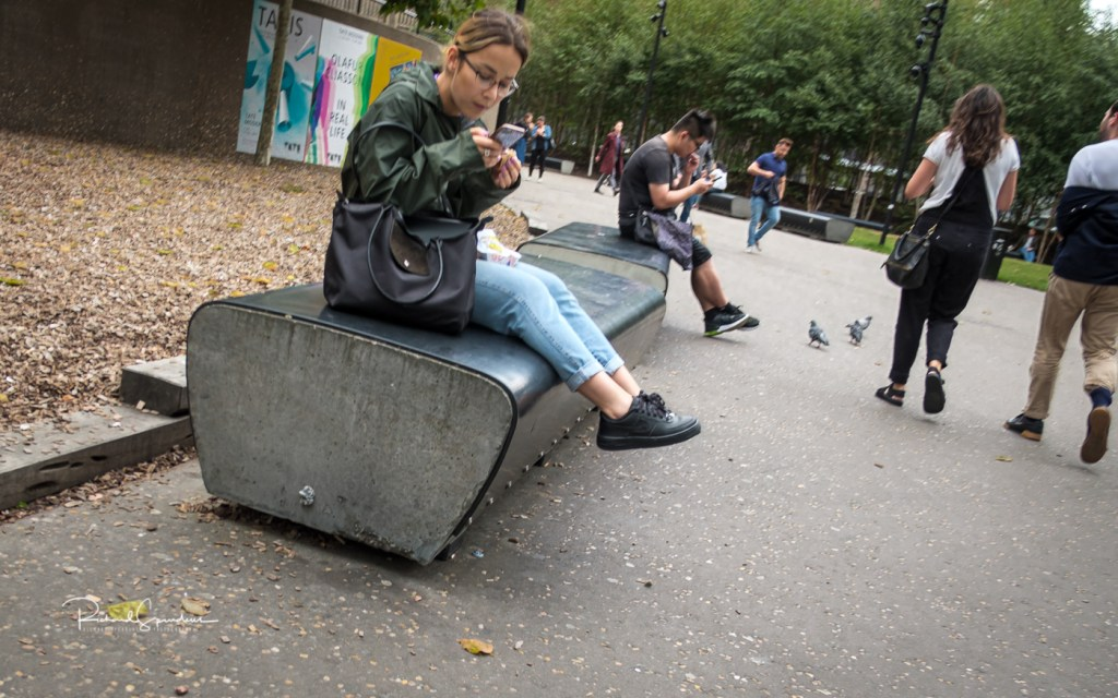 colour image of two people sat on a stone bench one at each end - both engaged with their phones. london views with my fuji xt-2