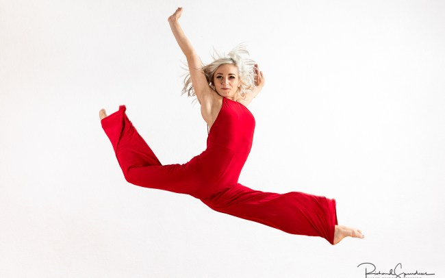 colour image of a dancer in a freeform leap wearing a red jump suit