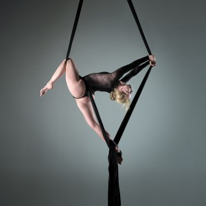 Colour image of aerialist fanny m holding a dynamic pose in mid air using aerial silks