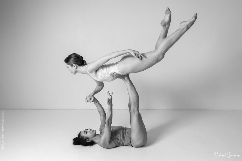 Dance Photographer - Dance photography - monochrome image of dancers poppyseed and jasmin one laying on her back holding the other on her feet above her