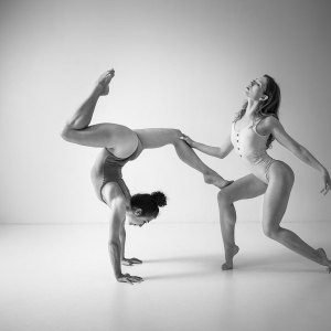 Dance Photographer - Dance photography - monochrome image of dancers poppyseed and jasmin who is holding a handstand with her legs at ninety degress and the second is holding her in balance making a strong body shape with legs and arms