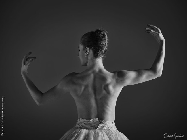 Dance Photographer - Dance photography - monochrome image of a dancers back as she holder her arms out to the side