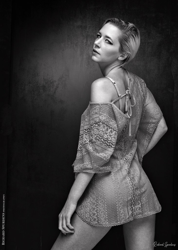 monochrome image from virtual shoot with amie boulton model wearing a textured dress looking back towards the camera over her left shoulder