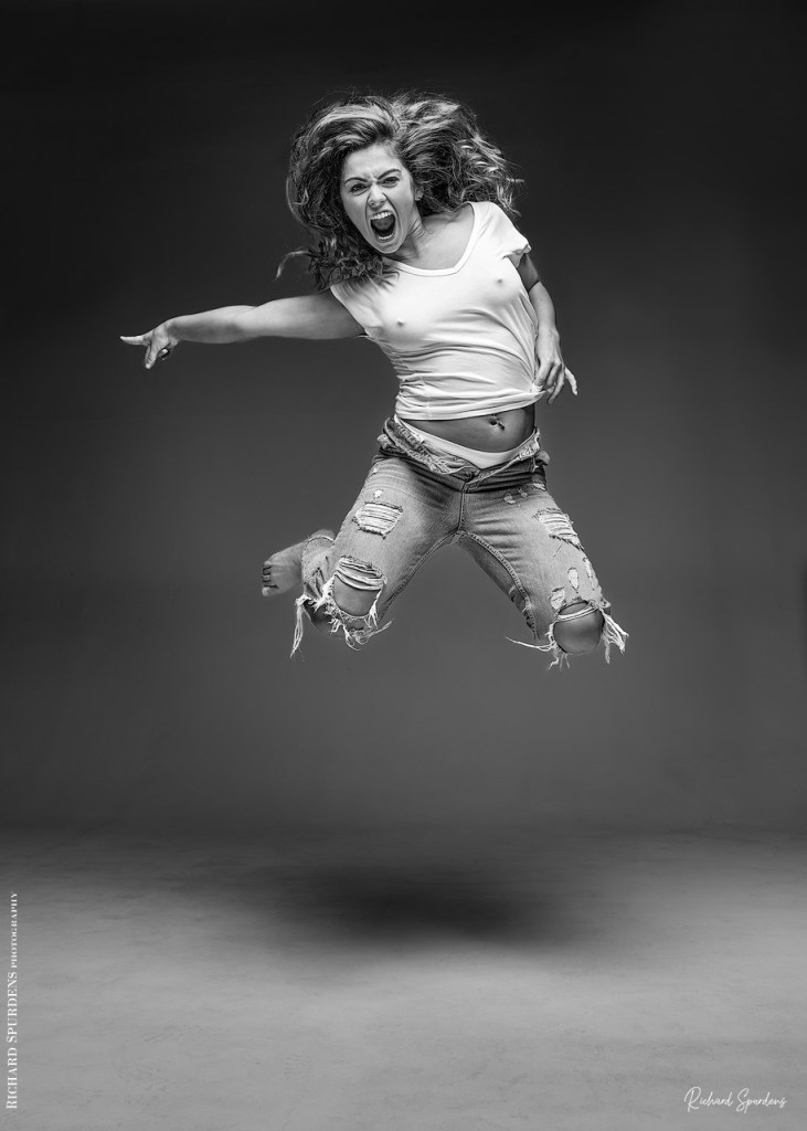 Fashion Photography - Fashion Photographer - monochrome image of natalia wearing torn jeans caught in mid air pointing out to the side of the her body