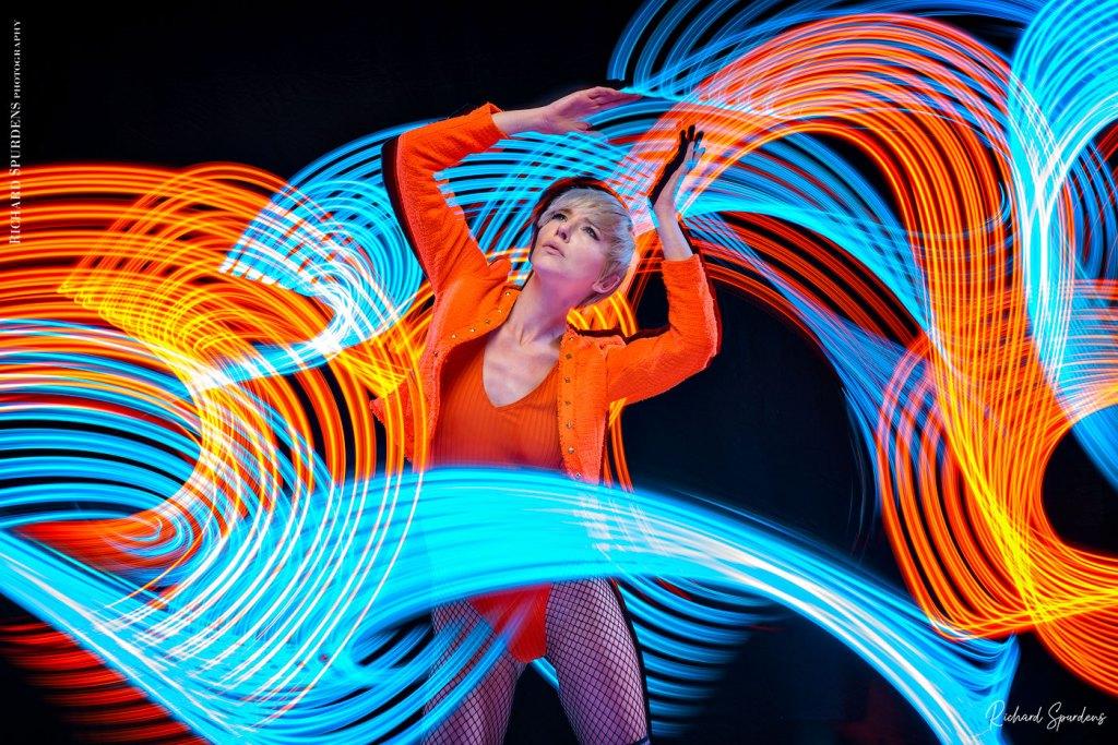 Fashion Photography - Fashion Photographer - colour image of model wearing orange jackets and body lighting swirls around the model using blues and orange lights wands around the model