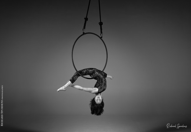 aerial arts photography - aerial arts photograher - monochrome image of aerial artist hang upside down in the splits the hoop