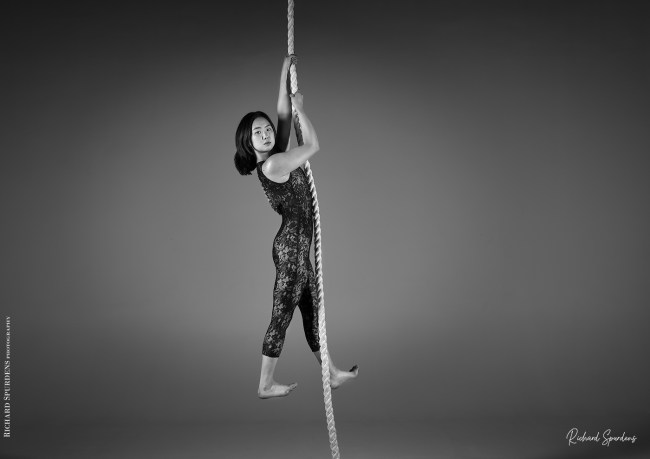 aerial arts photography - aerial arts photograher - monochrome image of aerial artists hang straight down from the rope holding herself up wthi her arms she is looking towards the viewer and her legs are held slightly apart with her feet turned up at the toes