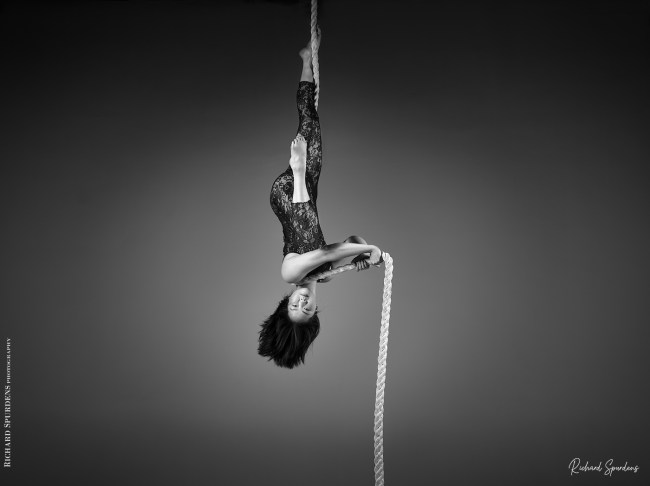 aerial arts photography - aerial arts photograher - monochrome image of aerial artist hang upside down from a suspended rope. one is straight up the rope and her foot is wrapped against the rope her other leg is bent in front of her a her foot is pointing straight up she is looking directly into the camera and is holding the rope out straight in both her hands as it then goes straight down to the floor