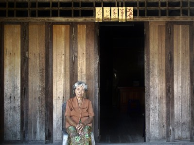 Old lady sitting quietly in front of a partially open wooden doorway