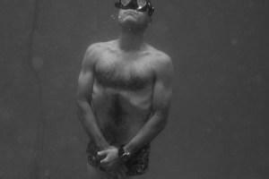 Adam Mooney standing on the bottom of the sea