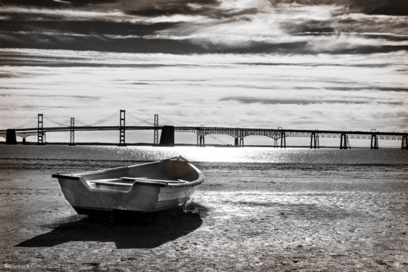 Boat on a beach with Chesapeake Bay Bridge in the background.