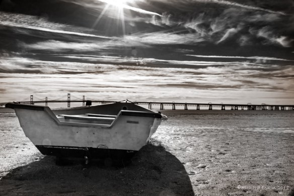 A small boat on the beach with the Bay Bridge in the background.