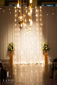 Cafe light backdrop and hanging over wedding ceremony