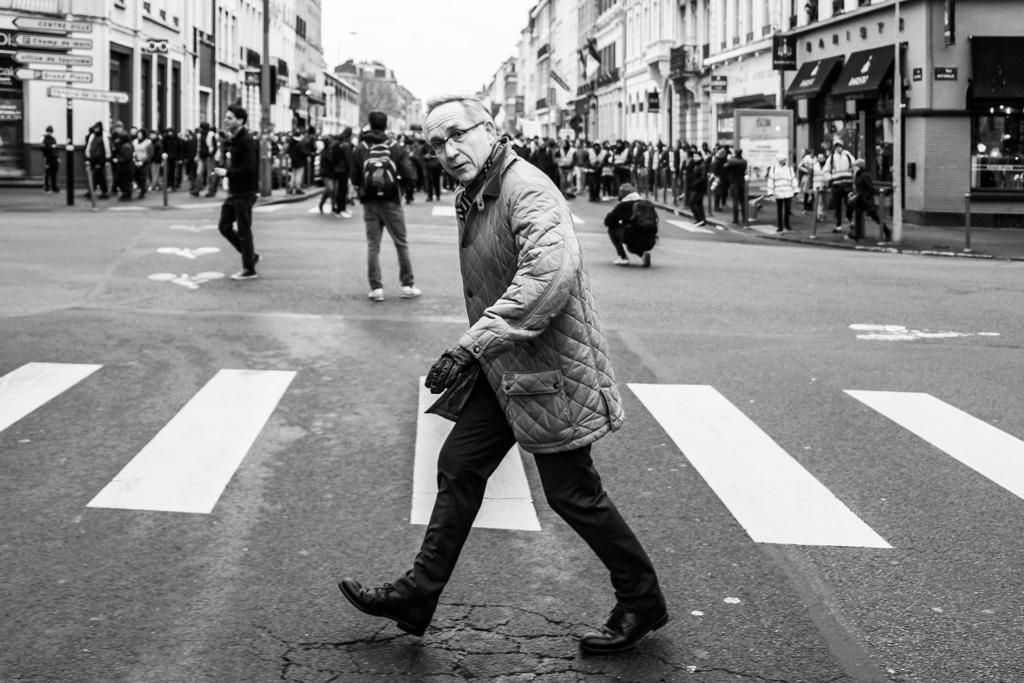 A man walking, a demonstration behind him