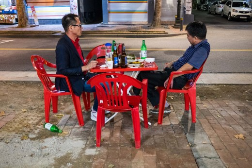 Two men eating on a street table