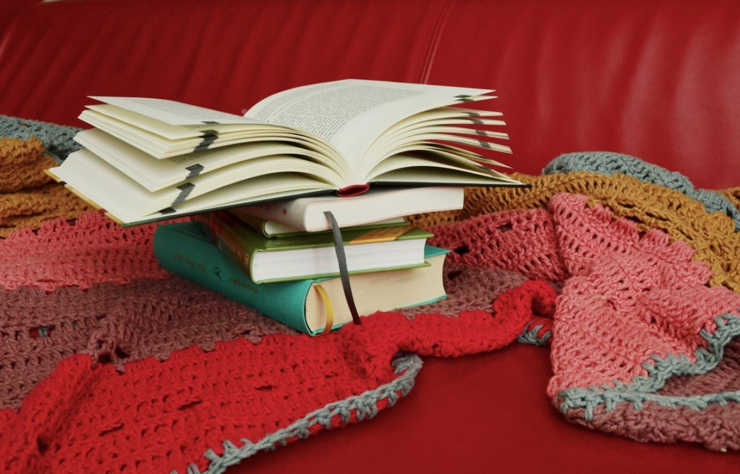 A pile of books stand on a blanket on the couch. An open book rests on top of the pile. Reading can support your therapy or counselling with Richmond Psychotherapy.