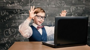 a happy kid wearing glasses and a bowtie in front of a laptop vocabulario in inglés