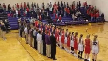 eagle grove and forest city basketball players and school officials show unity during the national anthem before their basketball game