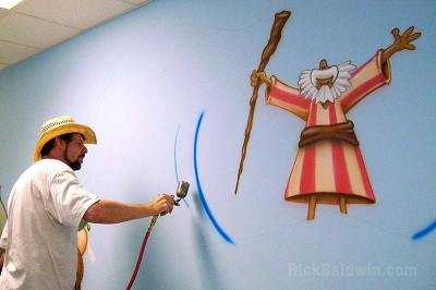 Painting a cartoon Moses mural