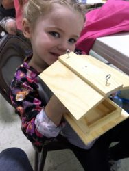 my daughter holding up a wooden bird feeder
