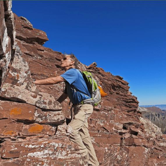 Rick Crandall climbing a steep, rocky slope