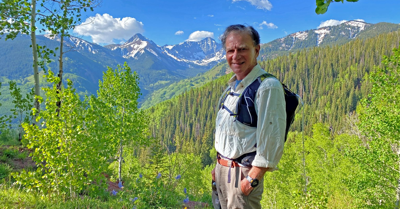 Rick Crandall at trailhead with mountains in the distance