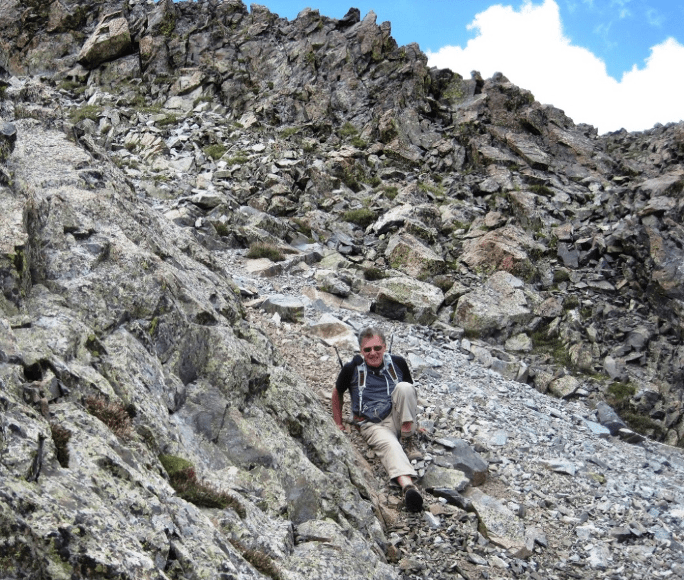 Rick Crandall sitting on a rocky path after slipping and falling.