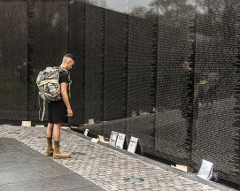 """The Wall, Washington, DC. First Prize in """"Emotion"""" digital competition at the Photography Club of Greater Cincinnati: judge Valda Halley's comment, """"I get an immediate sense of awe. This man seems to have traveled far with a mission to stand at this wall and pay his respects perhaps to a fallen brother or friend. As he stands reflecting on so many names and remembrances, his head bowed to look at the tokens and mementos left by visitors, I'm compelled to think on the lives that served. Good composition. Capturing the reflection off the wall gave the image depth both visually and conceptually. Good exposure. I like the muted colors."""". Sold as an exhibition item in the Mapleknoll Village art show. Received Judges' Commendation in """"Soldiers"""" contest on website Photocrowd."""