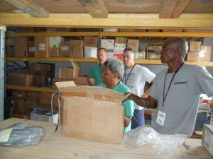 Dr. Deborah Turner of Des Moines and Dr. Murray Holcomb of Hutchinson, KS sort out supplies (both in scrubs)