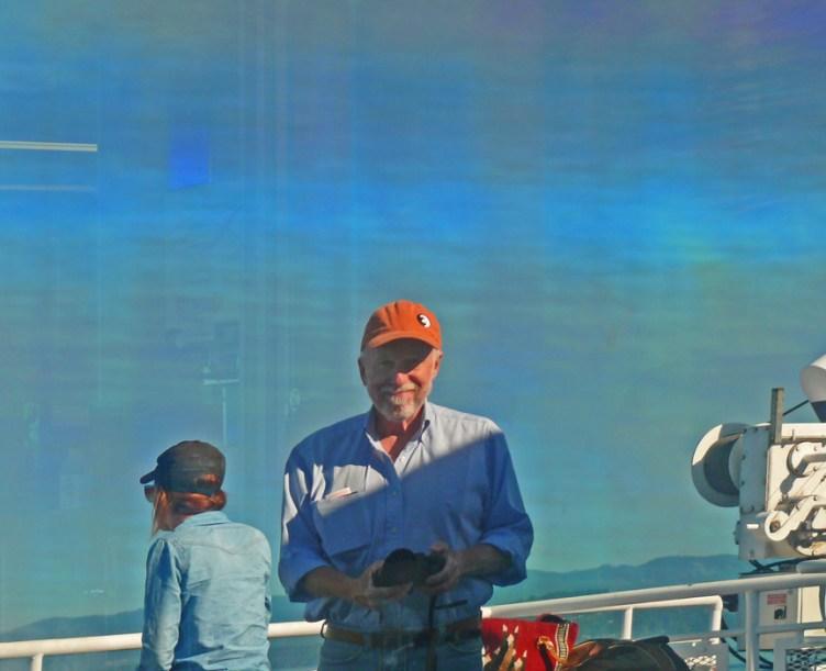 Self portrait reflected in ship's window.