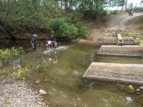 My wife Kay Pratt crossing the bridge out over a creek just north of Nashoba while Jim Finley stands by to help if needed.