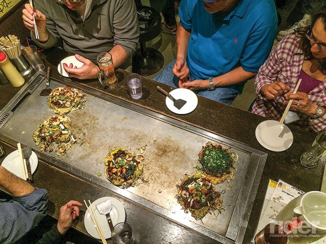 Okonomiyaki (seafood and noodle pancake) grilled at the table.