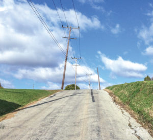 Telephone lines suggest the road will go slightly to the right just over the hillcrest.