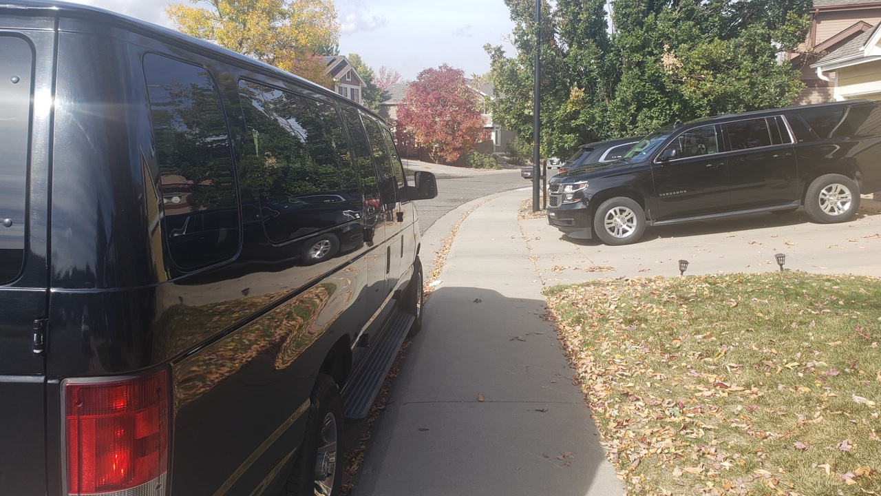 airport shuttle and black SUV waiting for customers