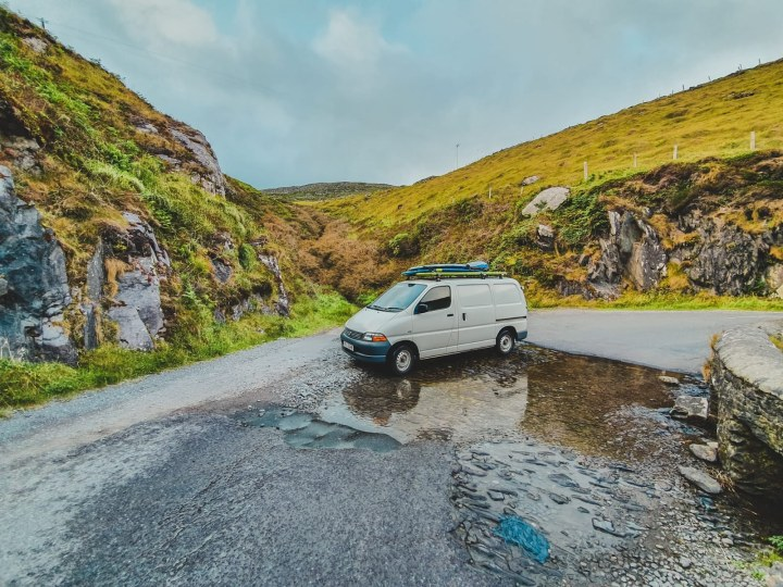Surfer couple travelling around Ireland in a Toyota Hiace with roof garden.