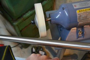 The barrel is secured in the polishing fixture and the 6″ hard felt wheel is treated with Polish-O-Ray. A gloved hand is used to slow the rotation of the barrel as it is polished.