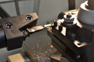 The knob is removed and tenon turned to the major diameter of the thread.