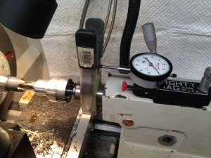 A dial indicator held in a magnetic mount is used to determine depth of cut. The spring clamp is attached to the tailstock quill.