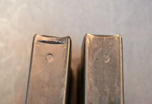 The AICS-AX magazine (left) has a small lip notched into the top front edge.  The traditional AICS magazine (right) does not have one.