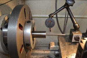 """I hold the barrel in the headstock of my G4003G lathe between two spiders.  A range rod with bushing is placed in the bore and I dial the bore in with a .001"""" indicator.   I then repeat the process with a .0001"""" indicator."""