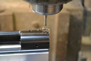 The end mill is run at a high speed and fed slowly.  The idea is to cut a new hole and not follow the old one.