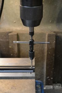 The tap is secured in in a tap handle and aligned over the hole with a spring loaded guide.